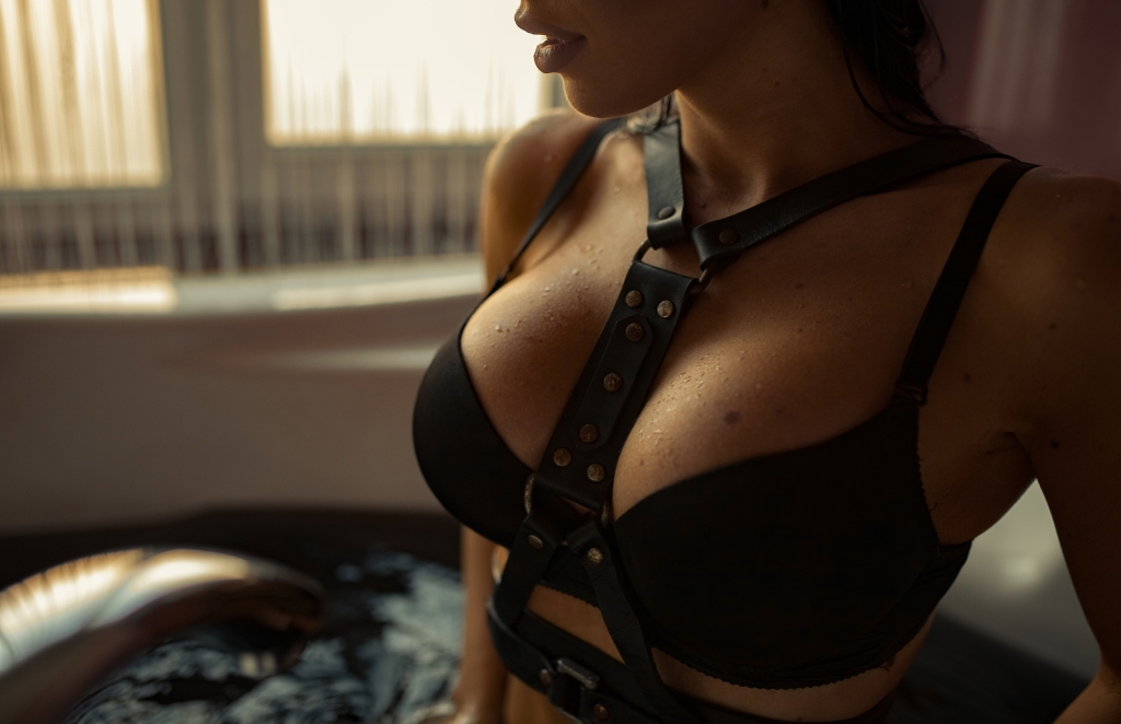 Woman in leather BDSM harness.