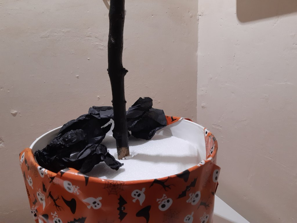 A painted branch pushed into polystyrene in a wrapped plaint container - a stand for Bat Bites.