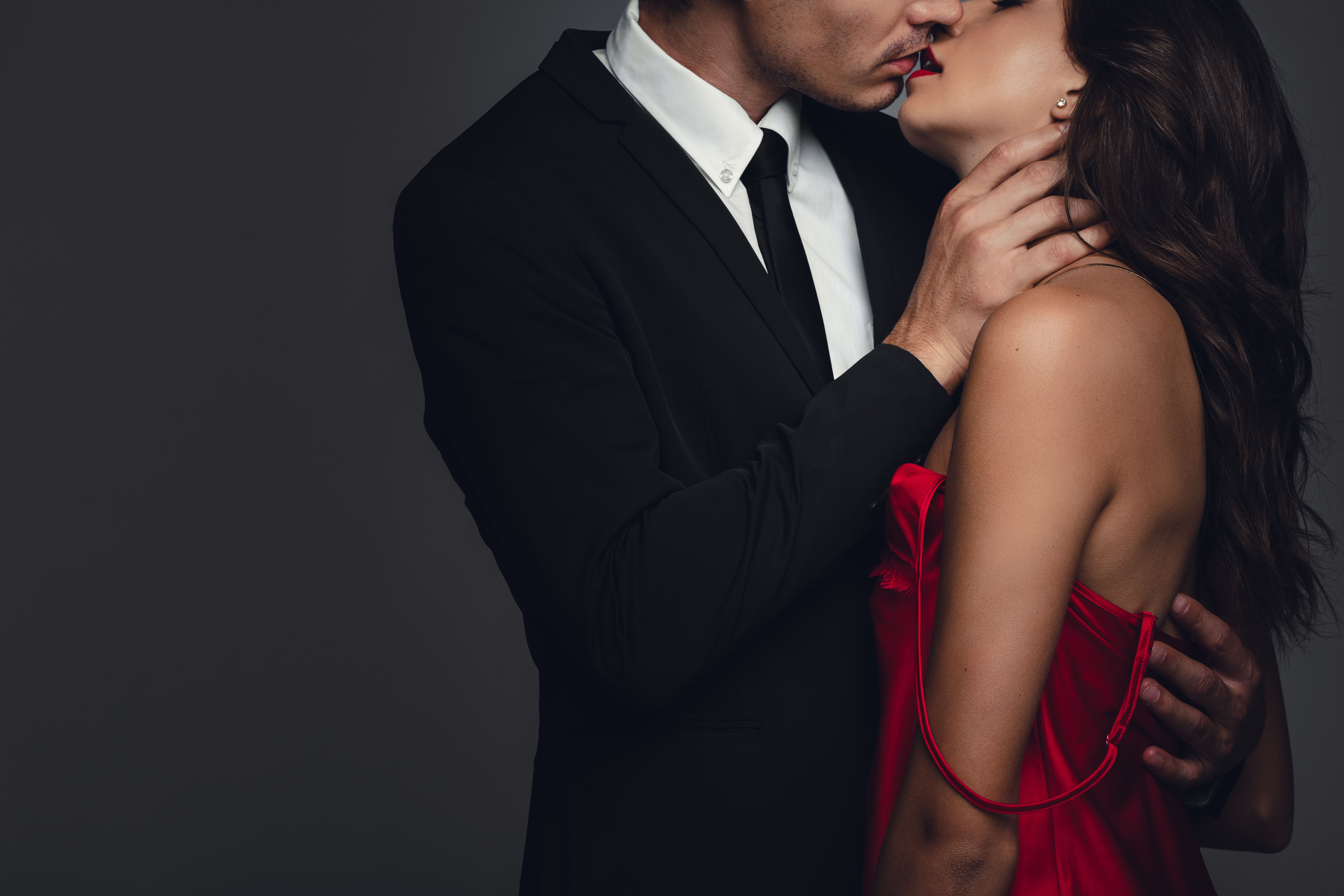 Formally dressed couple kissing.